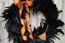 a bright Halloween wreath covered with black feathers, an orange glitter bow and a little broom is a gorgeous idea to rock