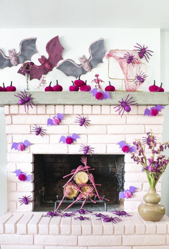 a bright and chic Halloween mantel with fuchsia velvet pumpkins, purple bats and spiders, pink skull hands and pastel bats