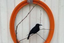 a bright and cool Halloween wreath of an orange picture frame, branches and a blackbird is a lovely and bold idea to rock