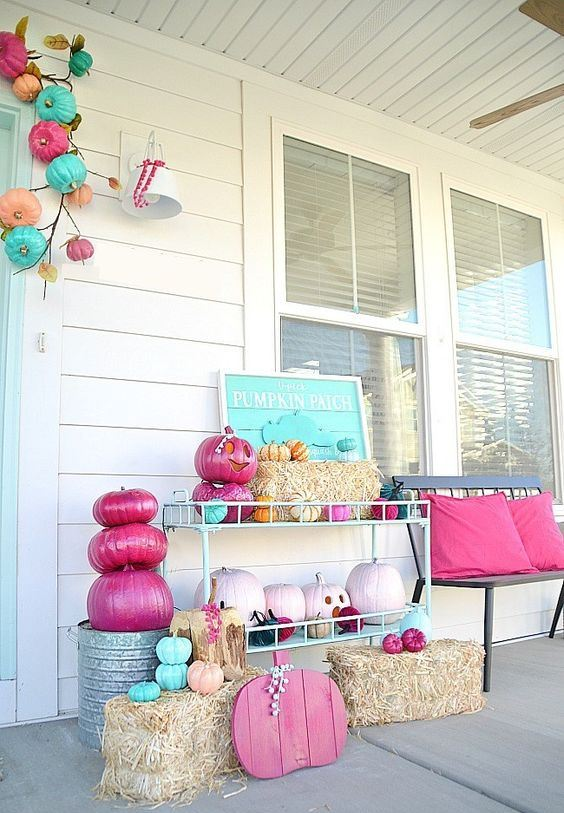 a bright and fun Halloween porch with turquoise, pink, blush pumpkins and signs and pillows