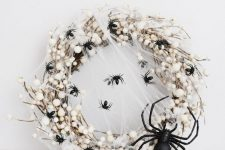 a catchy Halloween wreath of vine and berries, spider webs and mini black spiders plus a giant black spider is amazing