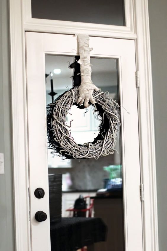 a catchy whitewashed vine wreath with a mummy hand holding it is a very creative and out of the box idea for Halloween