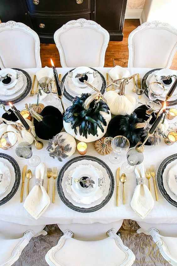 a chic Halloween tablescape with black and white pumpkins, feathers, candles, gold cutlery and candleholders