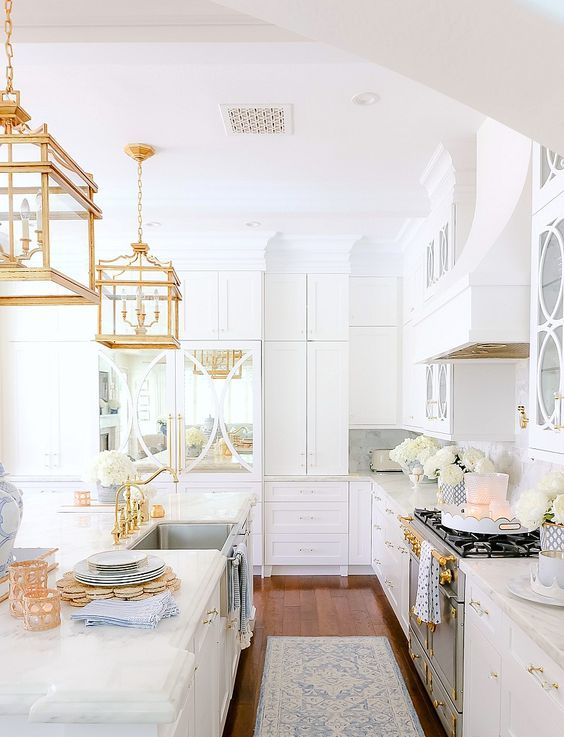a chic and glam white kitchen with gold fixtures, refined gold pendant lamps and gold handles is a very beautiful and refined idea