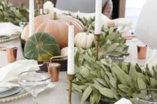 a chic modern Thanksgiving tablescape with a lush greenery runner, natural pumpkins and tall candles plus touches of copper