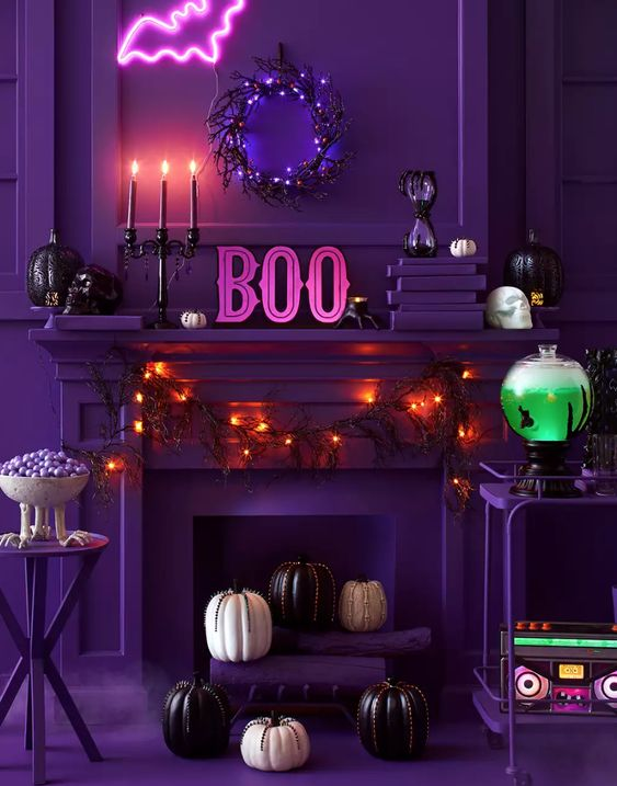 a chic purple Halloween space done with lights, pumpkins and black candles, a pink neon bat, a neon green drink in a tank