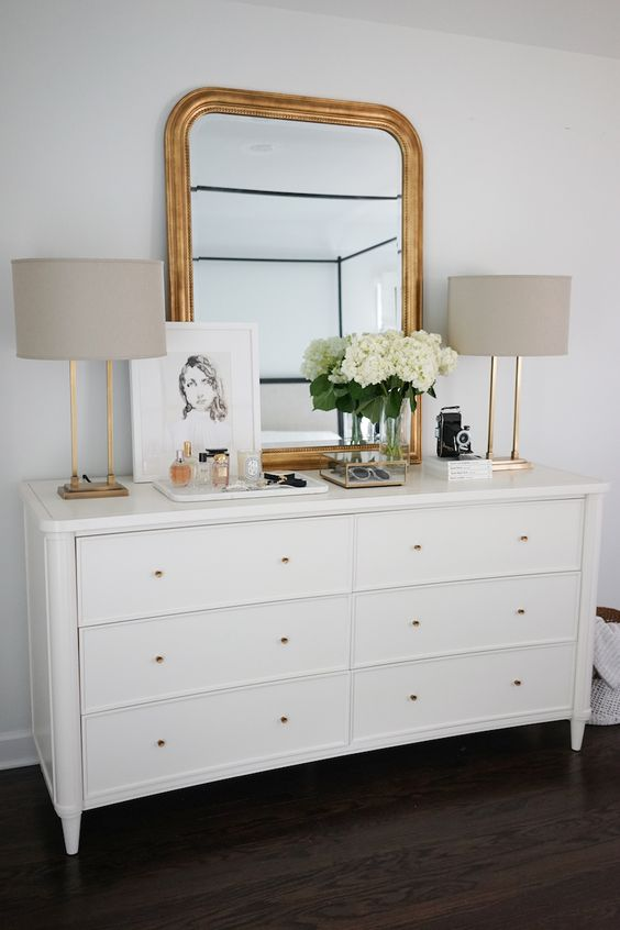 a chic white dresser with gold knobs, a mirror with a gilded frame, table lamps with gold bases is amazing