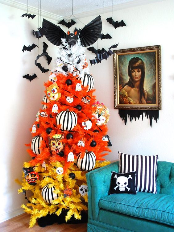 a color block Halloween tree in orange and yellow, with striped oversized ornaments, black ornaments and mini ghosts and bats over it