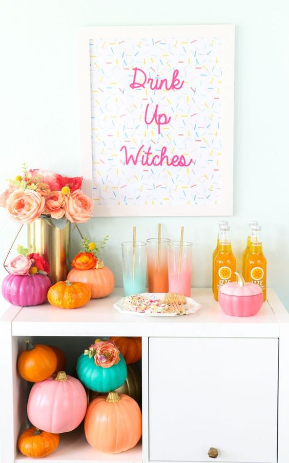 a colorful Halloween drink bar with bright pumpkins, ombre glasses and a sprinkle sign, a lush floral centerpiece