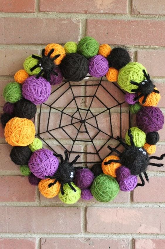 a colorful Halloween wreath of colorful yarn balls, yarn spiders and a spider web in the center is a cool and fun idea to decorate