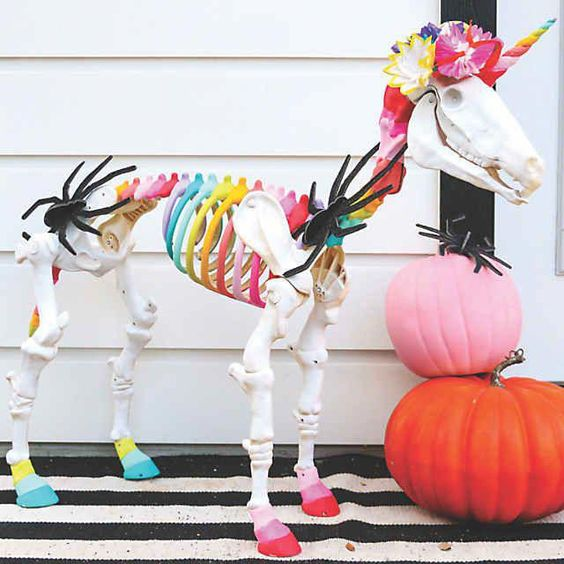 a colorful unicorn skeleton with bright stacked pumpkins is a unique Halloween decoration to rock