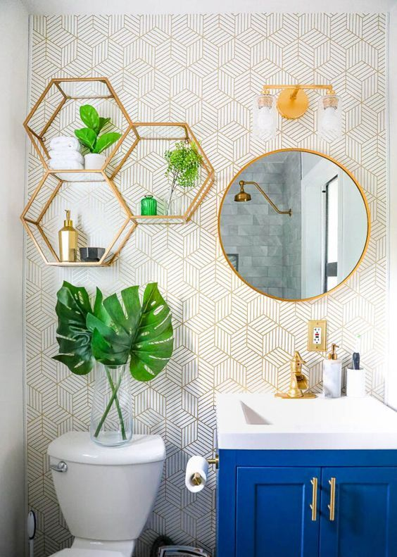 a cool bathroom with printed wallpaper, gold hexagon shelves, a round mirror in a gold frame, gold fixtures and handles is very bold