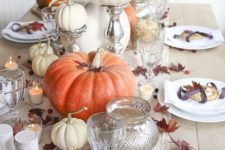a cute fall or Thanksgiving table setting with pumpkins, fall leaves, cranberries and mini pies for each place setting