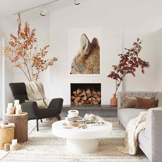 a fall Scandinavian living room with branches with leaves, faux fur, candles on tree stumps and a fox artwork