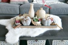 a fall centerpiece with wooden beads, natural and fabric pumpkins and red fall leaves in vases