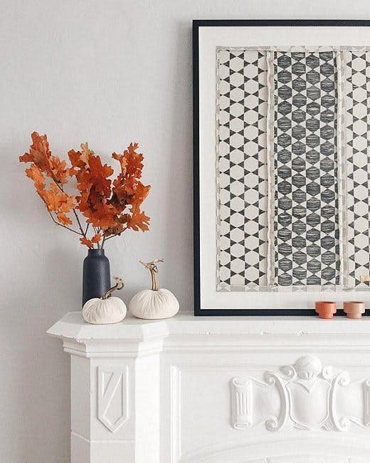 a fall mantel with a graphic artwork, fabric pumpkins and a black vase with fall leaves for natural decor