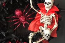 a fun Halloween wreath of black and red fabric blooms, a red glitter spider and pumpkins, a skeleton dressed in a red trench