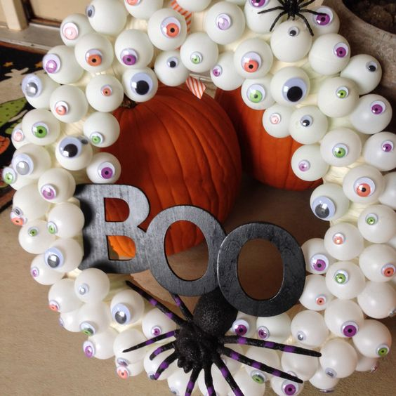 a fun Halloween wreath of googly eyes, a black spider and black letters is a gorgeous idea for styling for Halloween