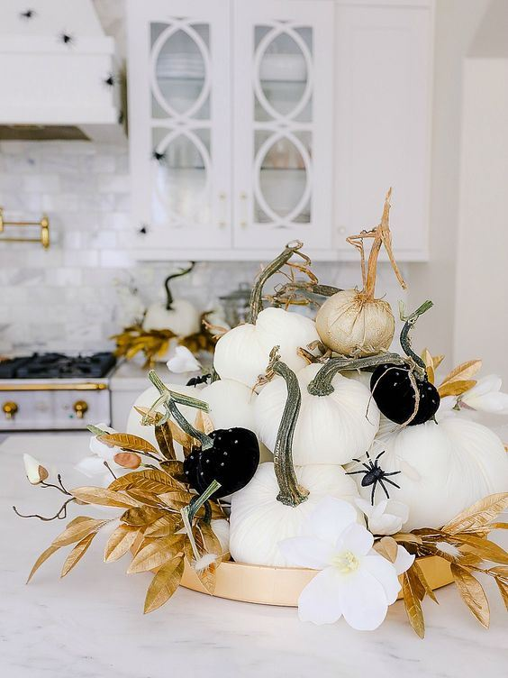 a glam Halloween centerpiece of white and black pumpkins with spiders, gold leaves and white blooms