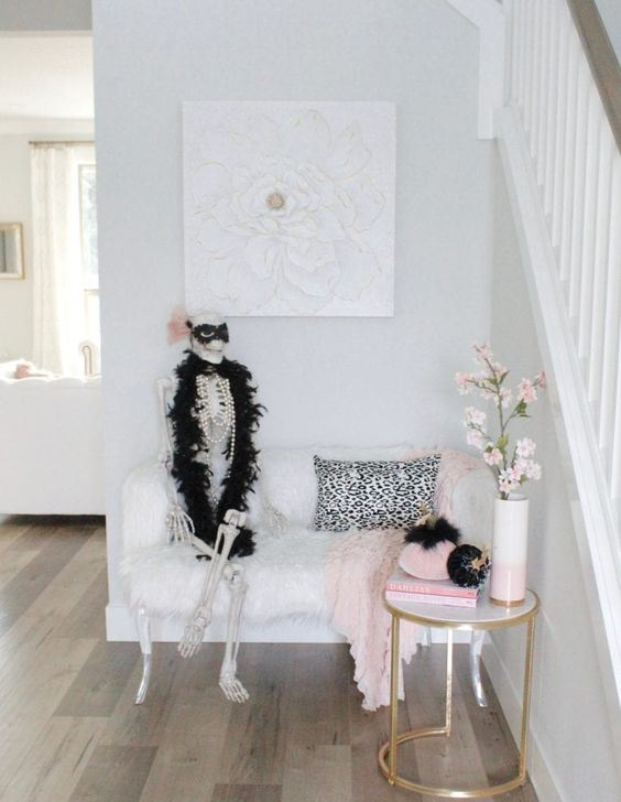 a glam Halloween entryway with a skeleton in pearls and fur, pink and black velvet pumpkins