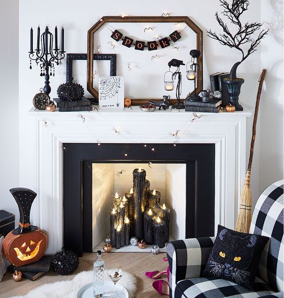 a glam Halloween fireplace with black glitter candles, a spooky tree, a banner, crows, a rhinestone pumpkin, cat pillows and lights