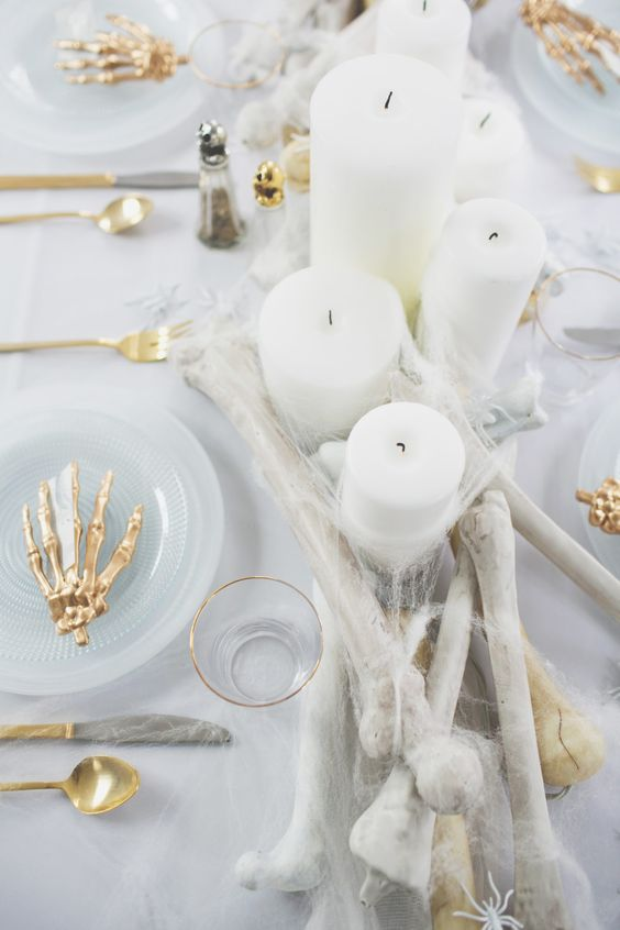 a glam Halloween table setting done in white, with bones, gold skeleton hands, candles and spiderwebs