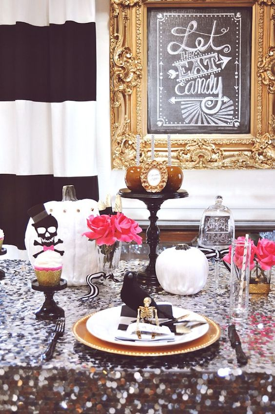 a glam Halloween table with a black sequin tablecloth, gold chargers and skeletons, pink blooms and white pumpkins