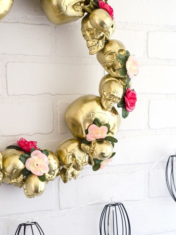 a glam Halloween wreath of gold skulls, pink and blush faux blooms and greenery is a pretty and lovely idea to rock