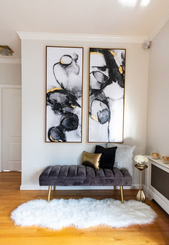 a glam and chic nook with a grey upholstered bench, statement watercolor artworks with gold, a gold pillow, legs and a small table
