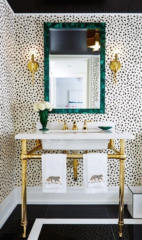a glam bathroom with Dolmatin walls, a gold sink stand, gold sconces and a mirror in a beautiful green frame plus a green vase