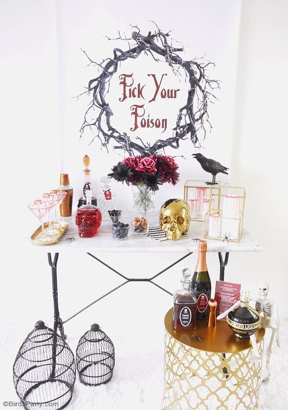 a glam cocktail nook with a gold skull, a crow, a bold floral arrangement, cages and a gold mini table