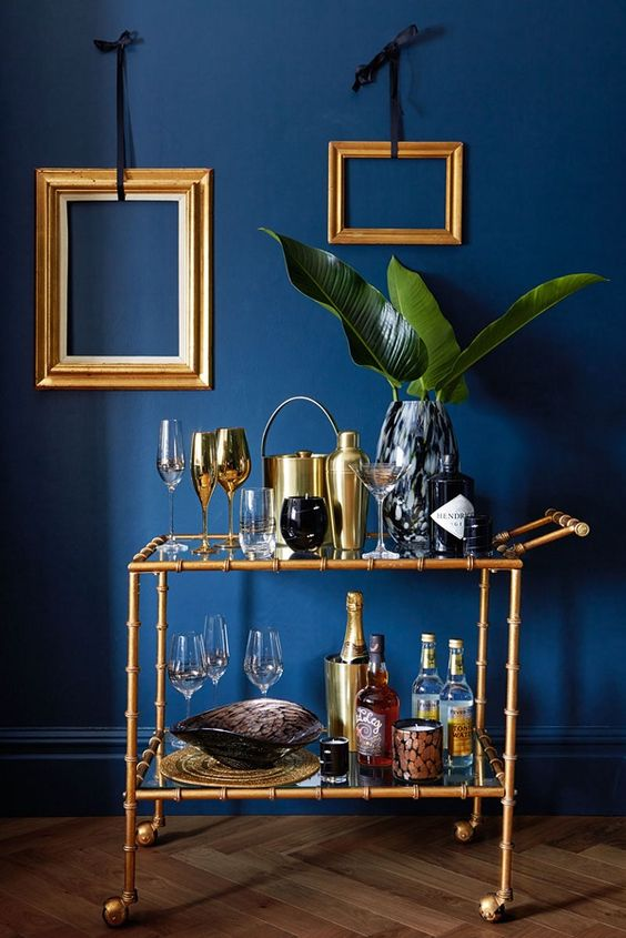 a glam nook with a navy wall, a gold bamboo bar cart, gold empty frame decor on the wall is amazing