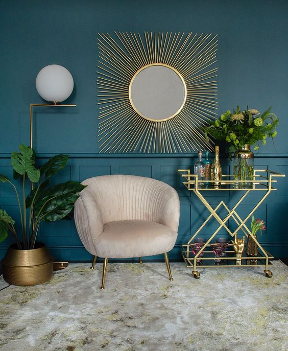 a glam space with a teal wall and paneling, a creamy chair, a gold bar cart, a gold planter, a mirror in a beautiful gold burst frame and a floor lamp