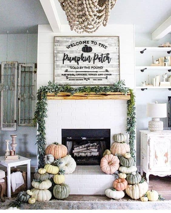 a greenery garland and stacks of natural pumpkins will make your fireplace more fall like at once