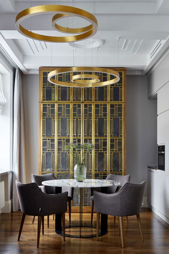 a jaw-dropping dining space with a gold and glass buffet, a marble table, grey chairs and gold circle pendant lamps