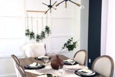 a laconic Thanksgiving tablescape with a eucalyptus arrangement, little white pumpkins, blakc plates and a fau fur runner