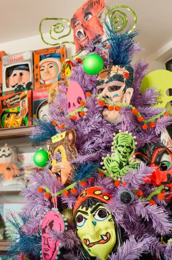a lilac Halloween tree decorated with non green, yellow and pink monster decor and masks is wow