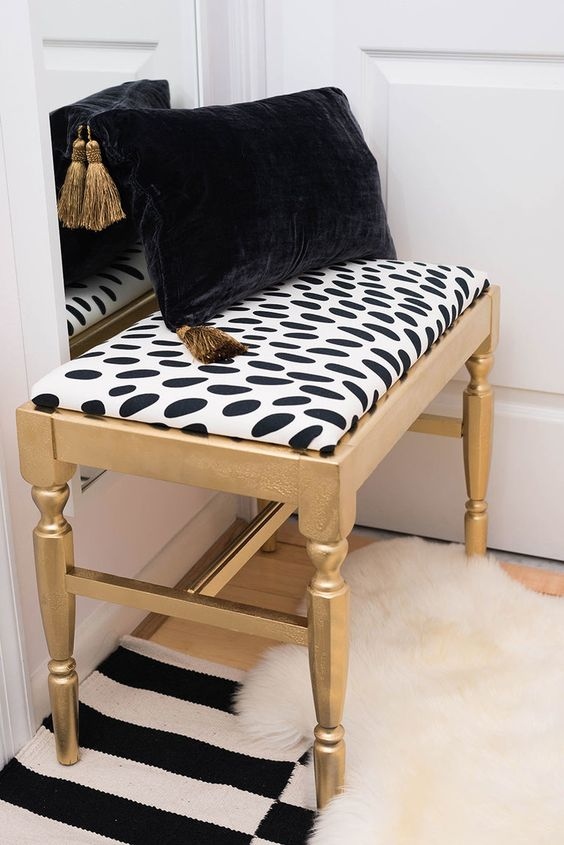 a lovely gold bench with a spotted seat, a black and gold pillow is a pretty idea for any modern glam room