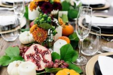 a lush table runner of foliage, berries, fruits, blooms, pillar candles and mini pumpkins for a Thanksgiving table