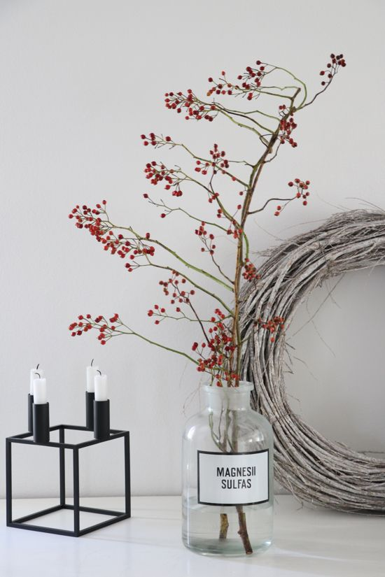a matte black candelabra with candles, branches with berries in a glass bottle and a whitewashed vine wreath