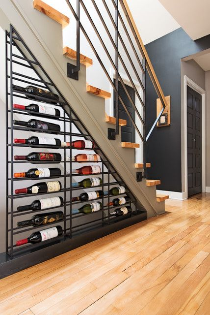 a metal shelf attached under  the staircase is a cool and bold idea that takes yoru wine on display