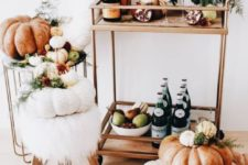 a modern Thanksgiving bar cart with a gilded cart, fall blooms, heirloom pumpkins and faux fur