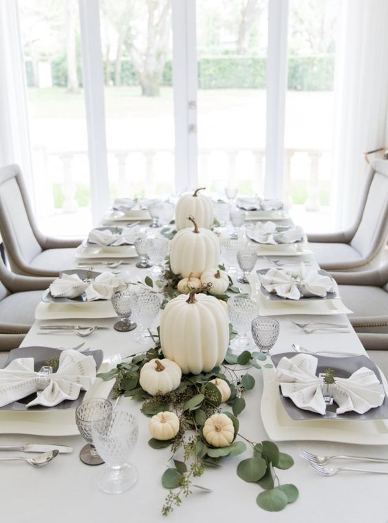a modern Thanksgiving table with white pumpkins and eucalyptus, grey glasses and plates and all white everything