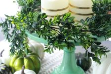 a modern and simple Thanksgiving centerpiece of a green stand, striped pillar candles, greenery, white and green pumpkins