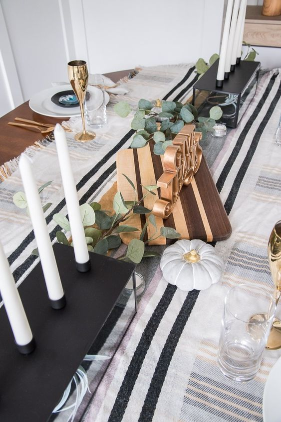 a modern classic Thanksgiving tablescape in black and white, with tall candles, eucalyptus, faux pumpkins