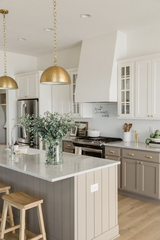 a modern farmhouse kitchen with white and taupe cabinets, white tiles and countertops, gold metal pendant lamps and gold fixtures