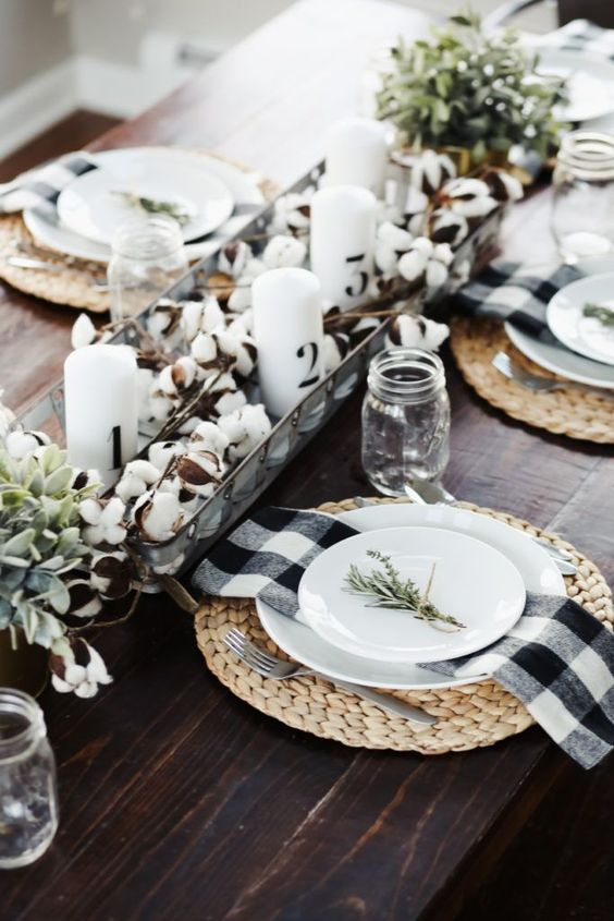a modern farmhouse table with cotton, candles, woven placemats, greenery and buffalo check napkins