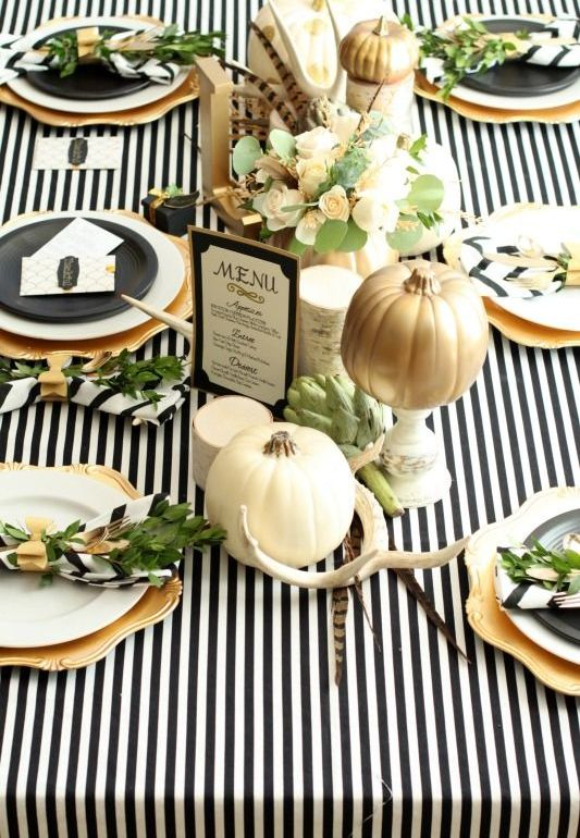 a modern glam tablescape with a black and white striped tablecloth, antlers, aux pumpkins, florals and gold chargers