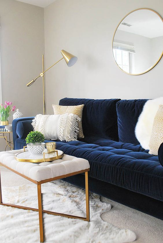 a modern living room in neutrals with a navy velvet sofa, a white pouf with gold legs, a gold floor lamp and a round mirror