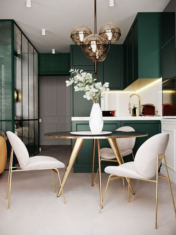 a modern refined space with dark green cabinets, a gold round table, creamy chairs with gold legs and gold fixtures that tie up two zones